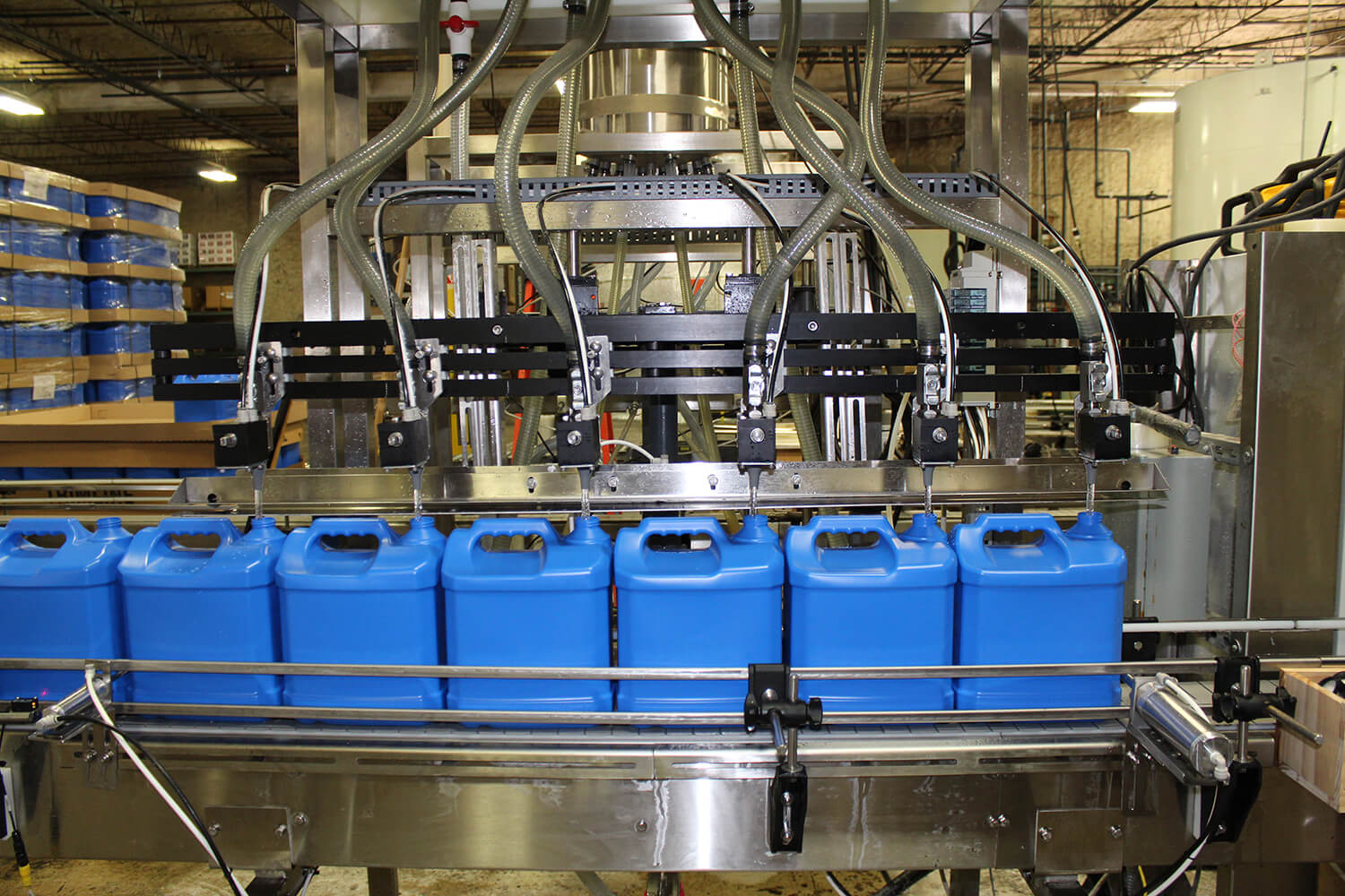 Blue containers being filled with liquid on a conveyor at a packaging plant